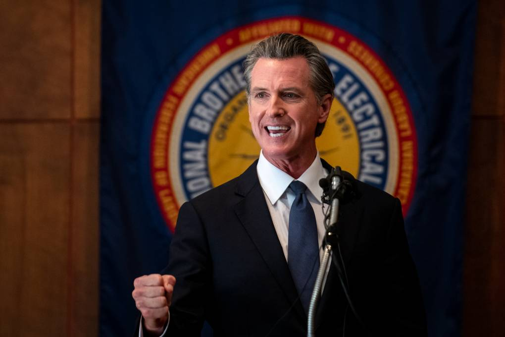 Gov. Newsom speaks flexing his right fist in front of an IBEW union symbol.