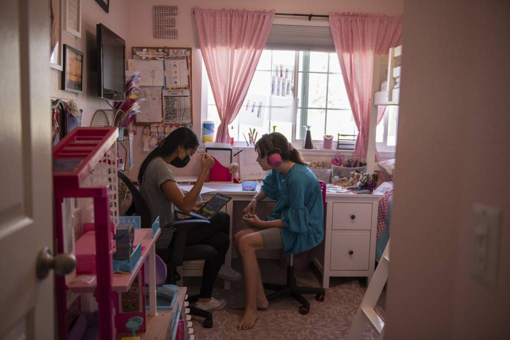 A teenage girl wearing large pink headphones sits in a pink bedroom with a woman holding a laptop.