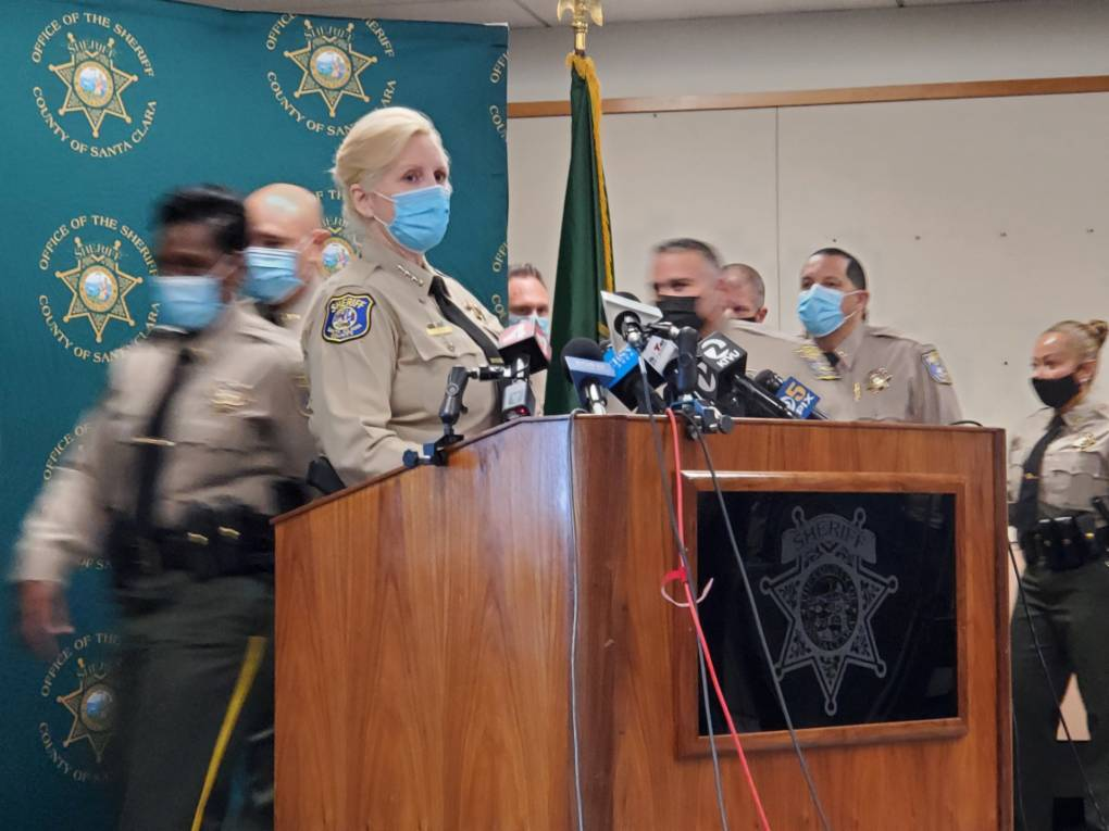 The female sheriff, in a light brown uniform and wearing a mask, flanked by many staff members in the same outfit, stands at a podium inside.