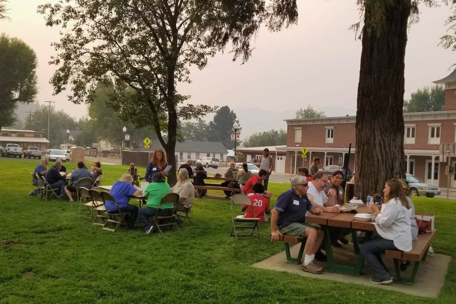 People sit at a group of picnic tables on a green lawn beneath tall trees.