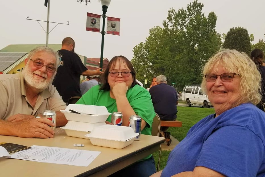 Three people sit at an outdoor table amid Styrofoam containers and soda cans.