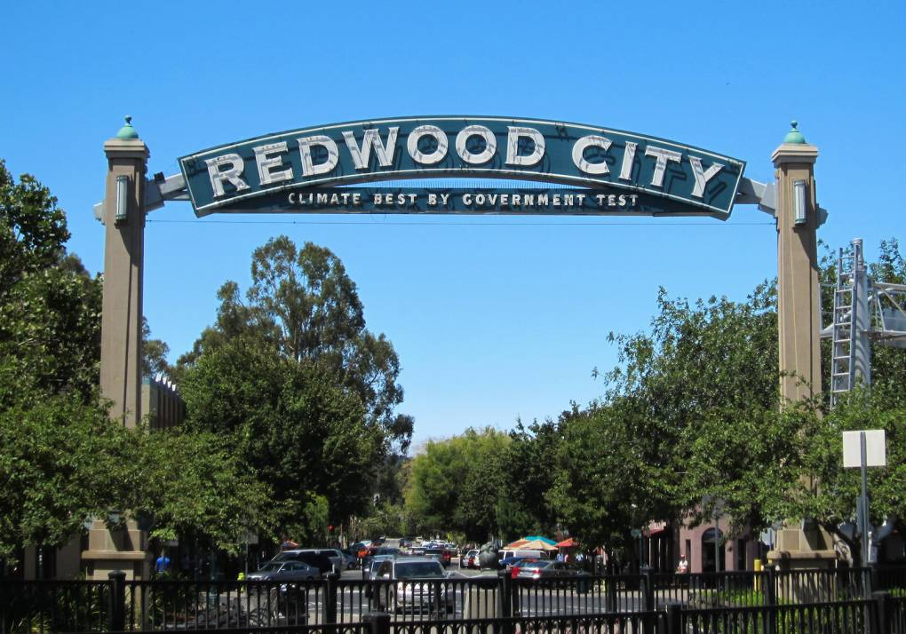 """A long sign across a leafy street that says """"Redwood City,"""" with the famous slogan in smaller type beneath."""