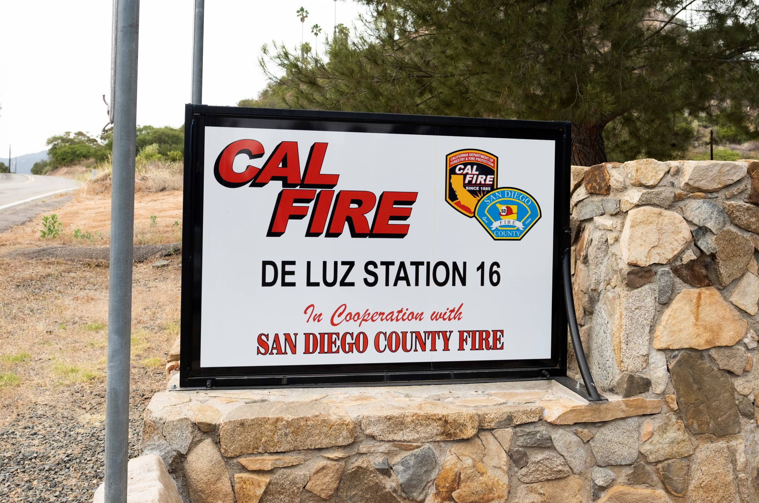 A sign that reads, 'Cal Fire De Luz Station 16' next to a country road.