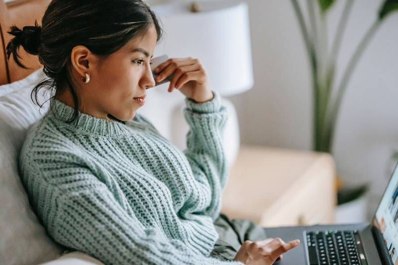 A woman in a green sweater sits on a couch using a laptop.