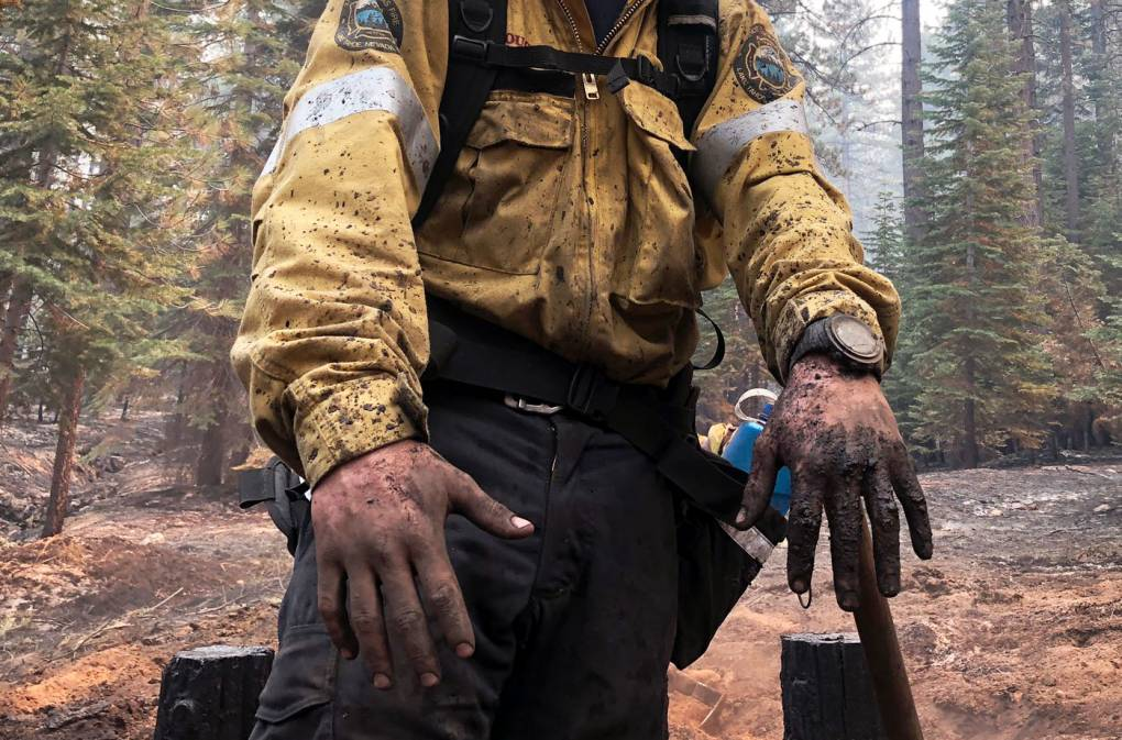 Close-up of a firefighter's dirty hands and clothing.