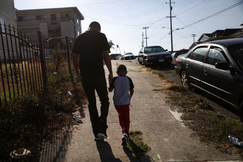 A man and young boy hold hands as they walk in silhouette on an urban sidewalk in early morning sun.