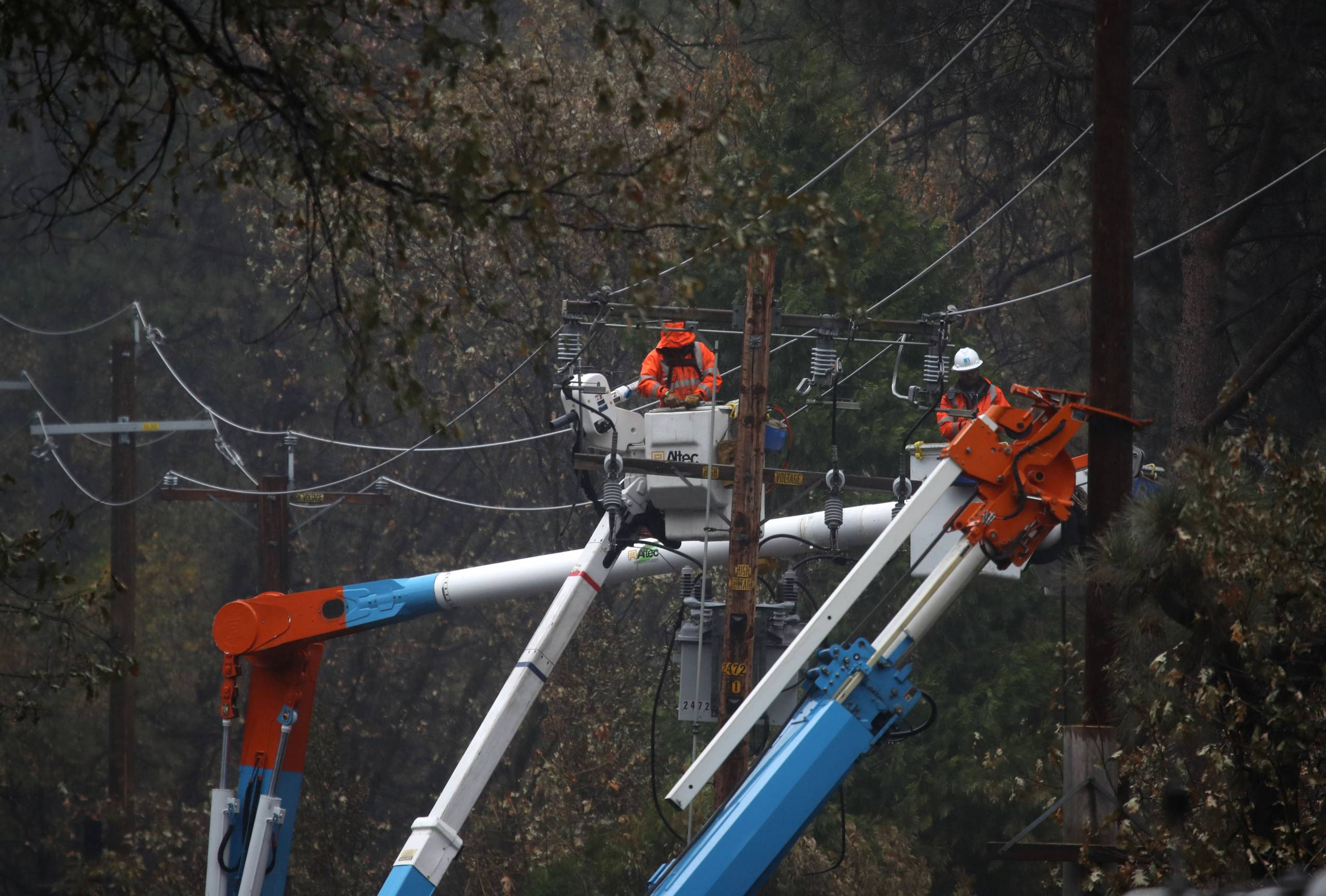One worker is on top of a crane next to a power line.