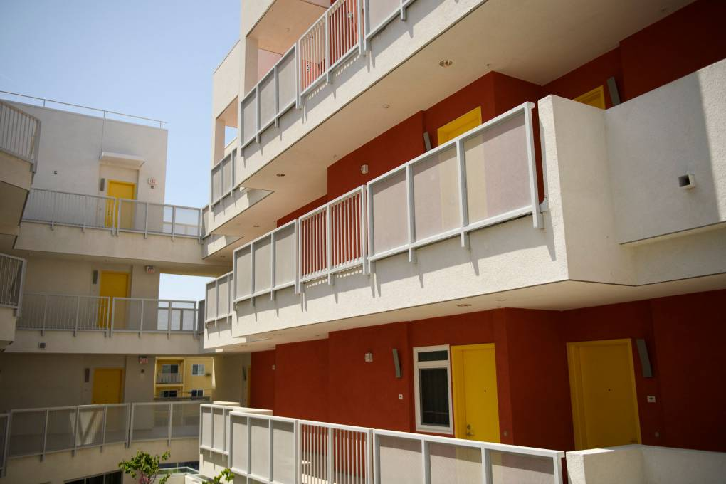 An exterior view of bright, modern-looking balconies on a high rise apartment building.