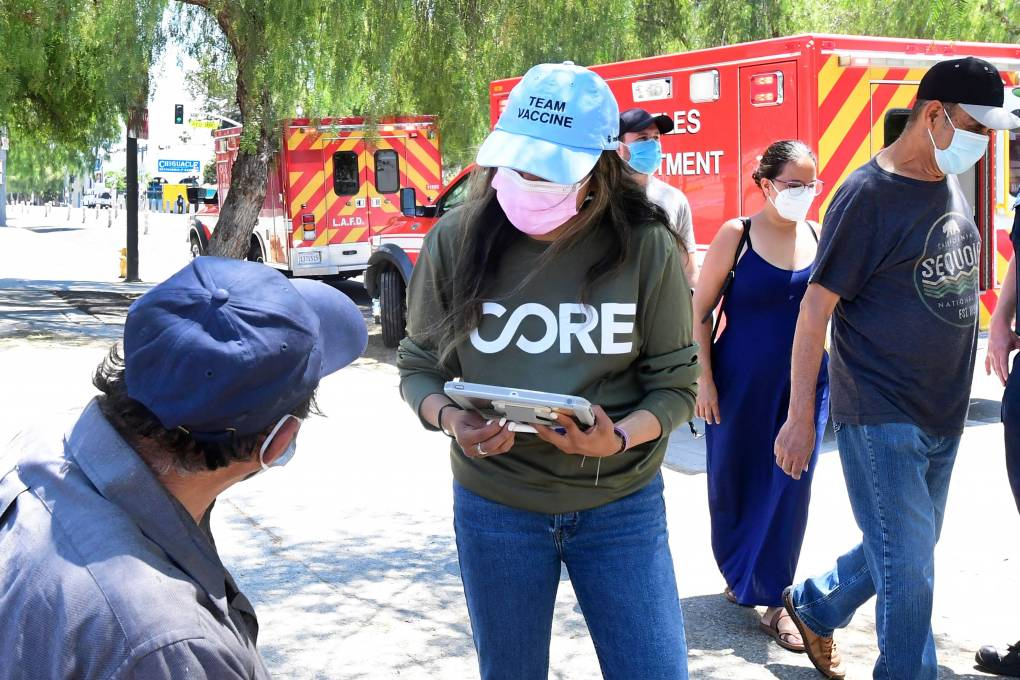 Woman in baseball cap and mask, holding clipboard, leans over to talk to man in baseball cap near two ambulances parked on a street.