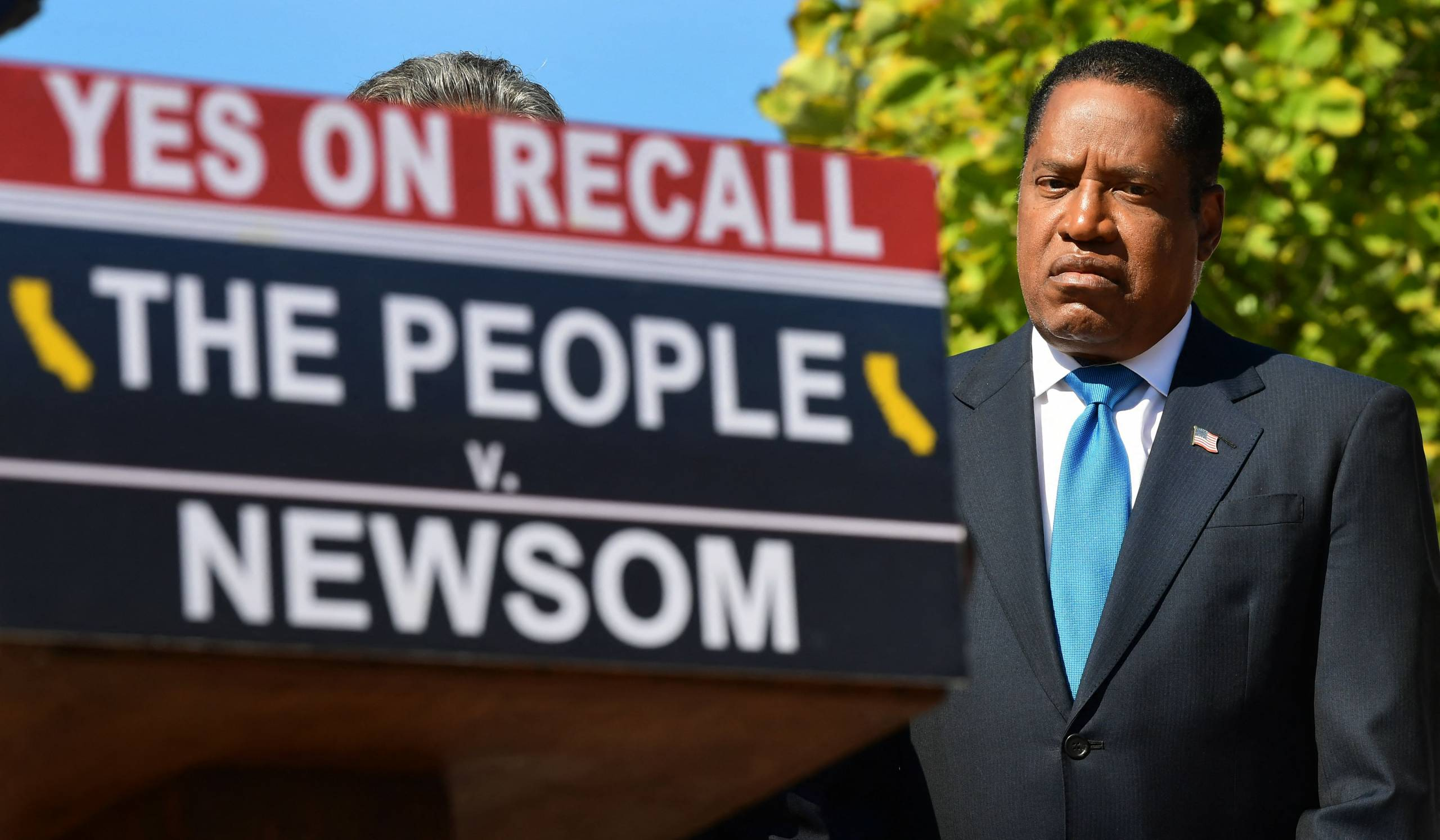"""Larry Elder stands near a podium sign that reads, """"Yes on Recall, The People v. Newsom."""""""