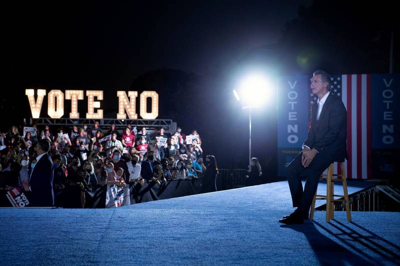 """Gov. Gavin Newsom sits on a stool and behind him is a crowd at his rally, also visible is a """"Vote No"""" sign."""