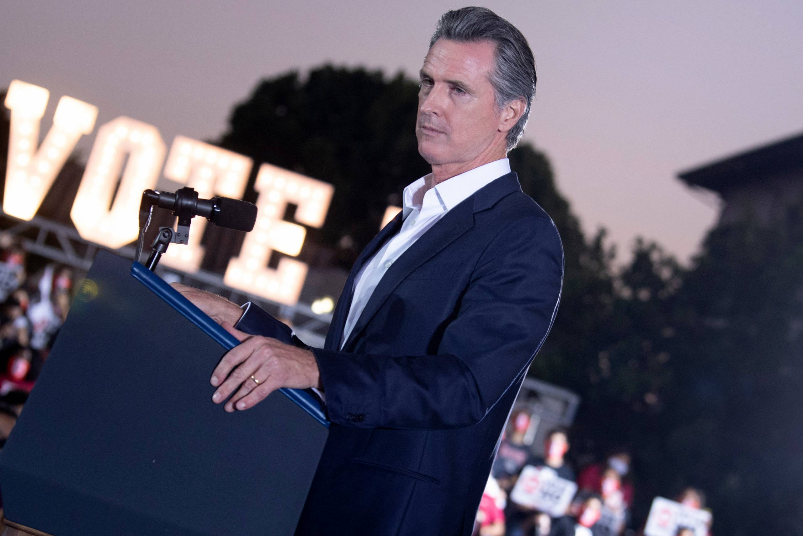 """Gov. Gavin Newsom stands at a podium with a stern look, a large lighted sign beyond him that says, """"Vote."""""""