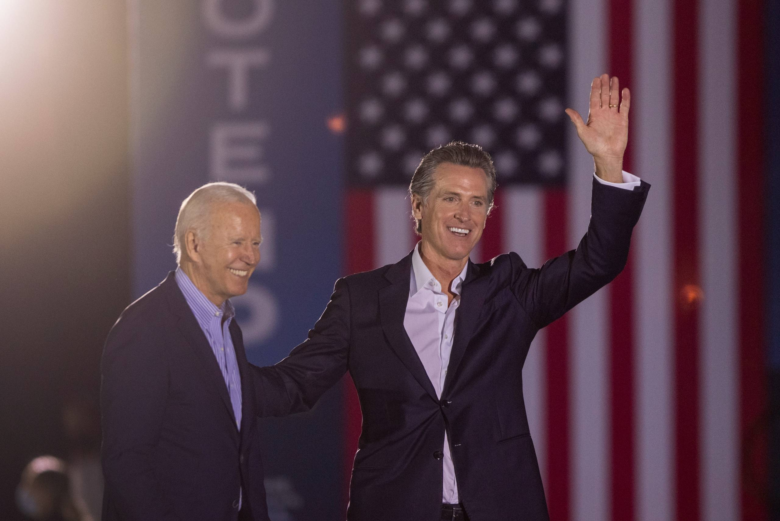 President Joe Biden and Gov. Gavin Newsom, waving, smile as they stand stand before an American flag.