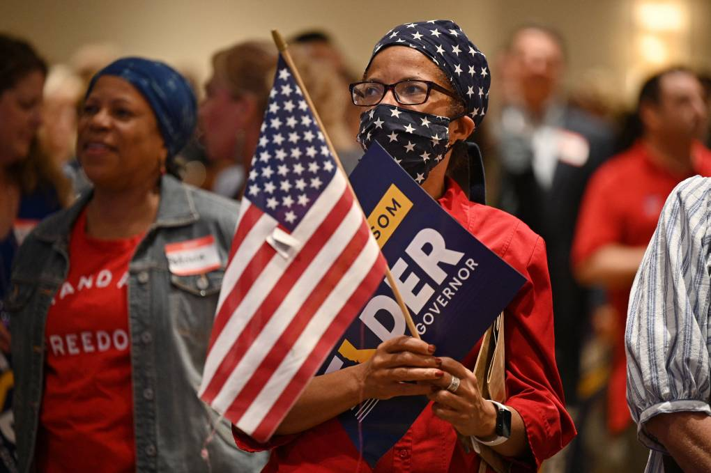 A person clutching an American flag and a Larry Elder poster wears a face mask and bandana printed with the flag.