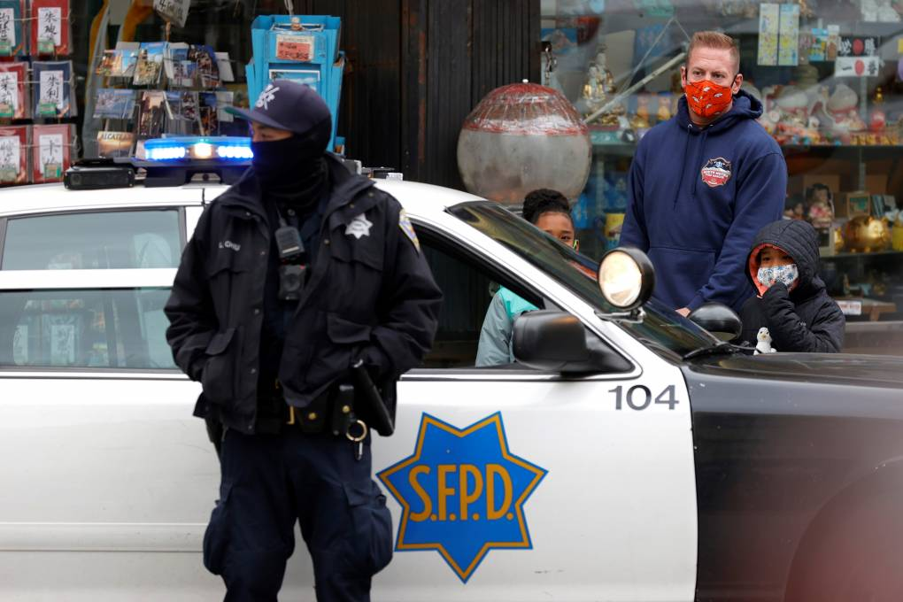 A police officer in a black face covering leans against his car door as a man with two small kids stands on the other side of the car.