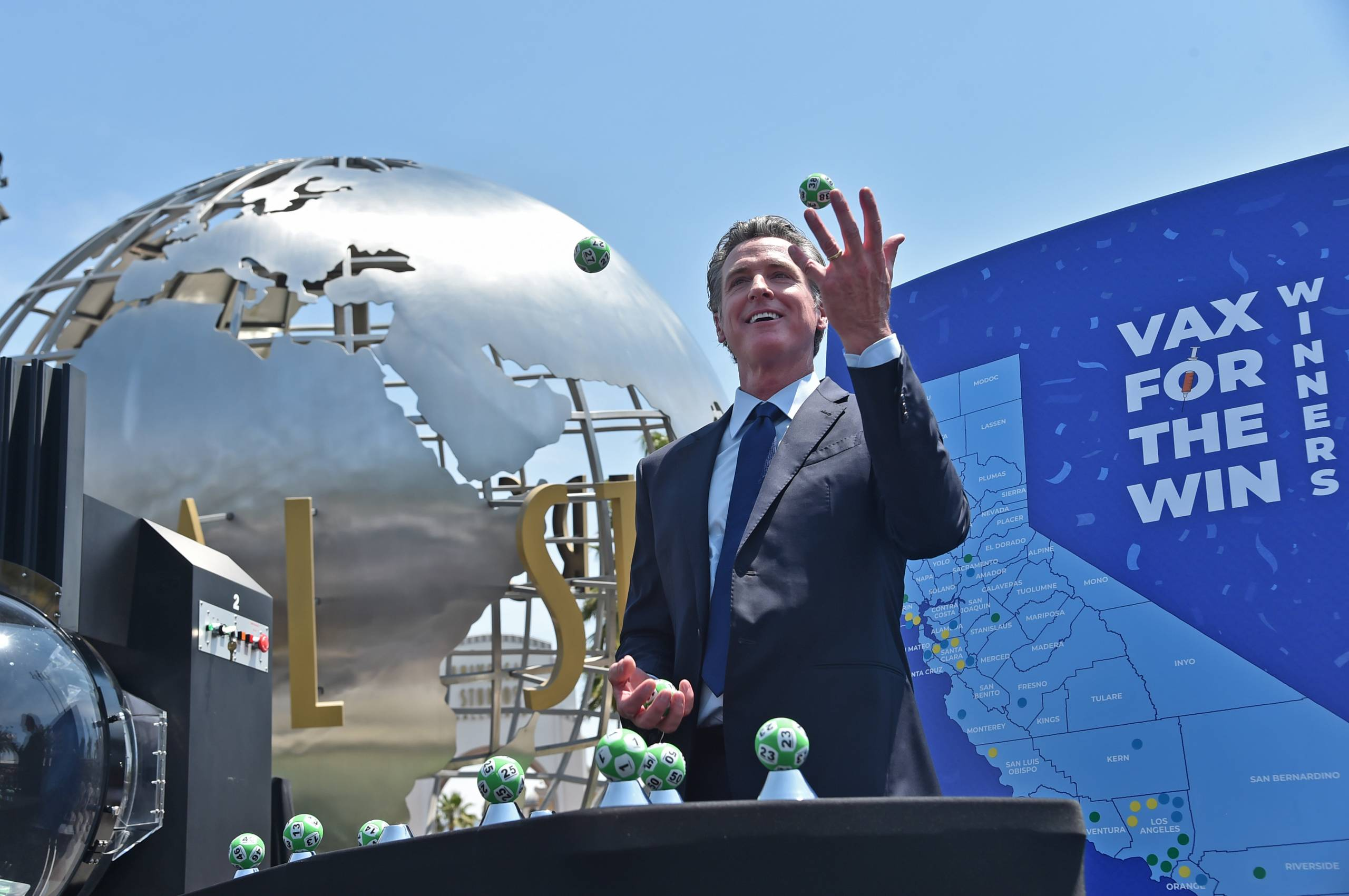 Gov. Newsom throws a few small lottery balls into the air in front of the Universal Studios globe statue.