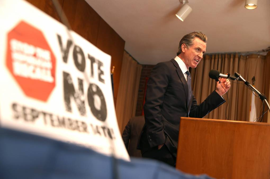 Gov. Newsom brandishes a fist as he speaks at a podium in from a Vote No sign.