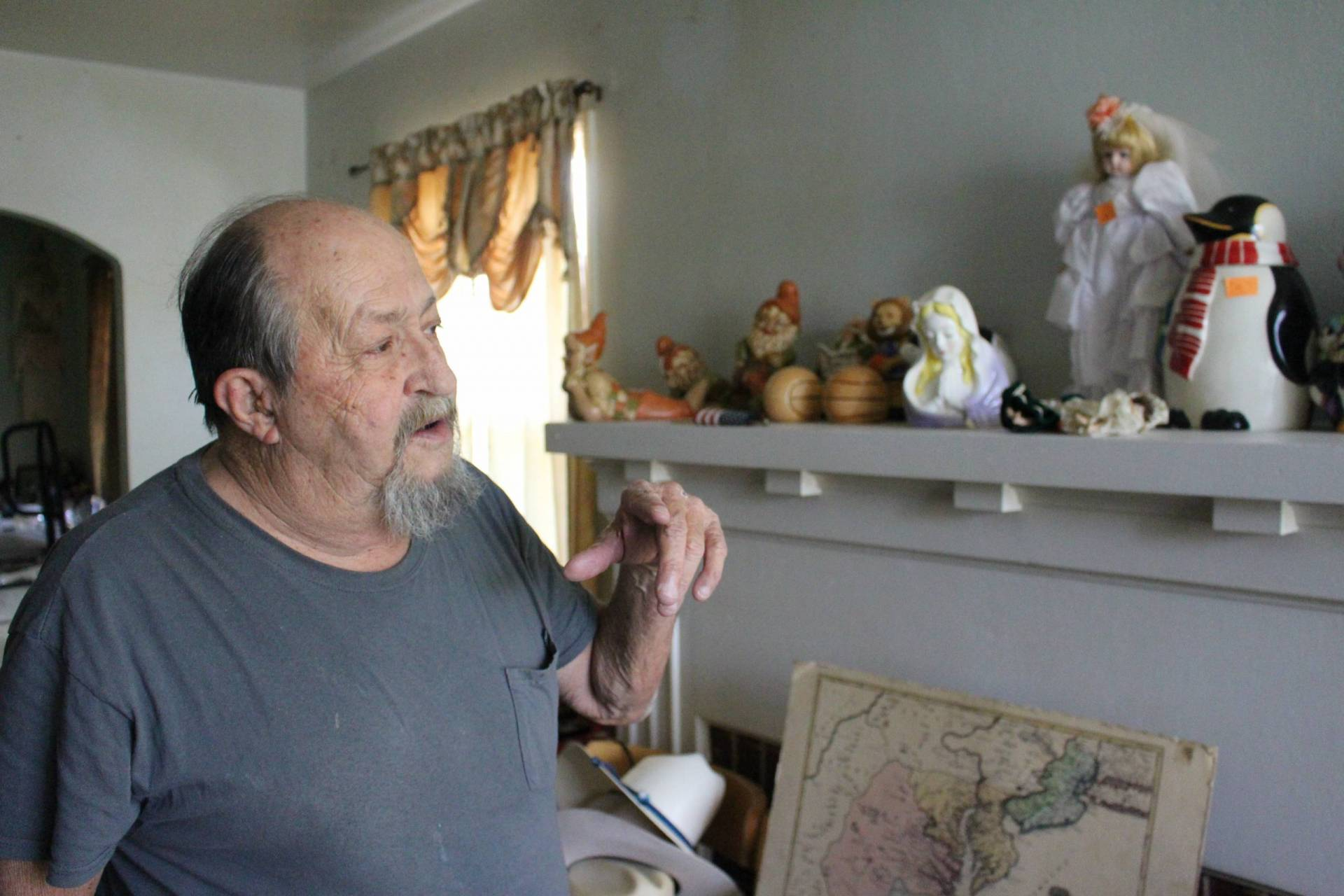 A man at his home pointing to animal-shaped cookie jars on a shelf.
