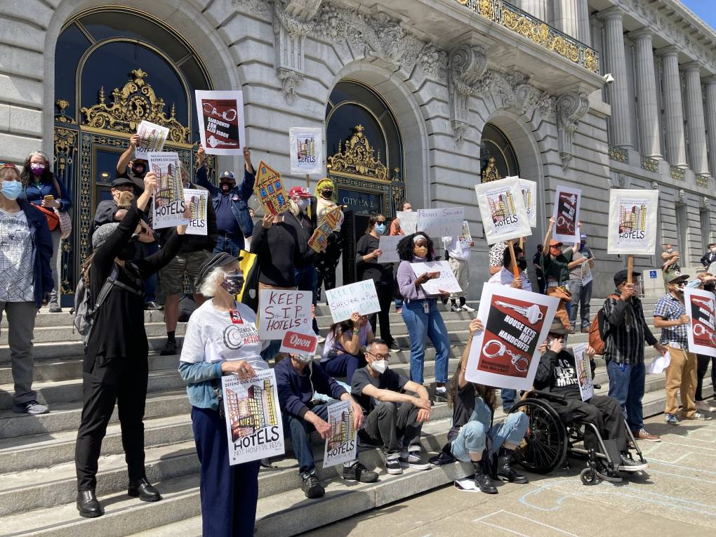 Advocates with posters demonstrate outside San Francisco City Hall.