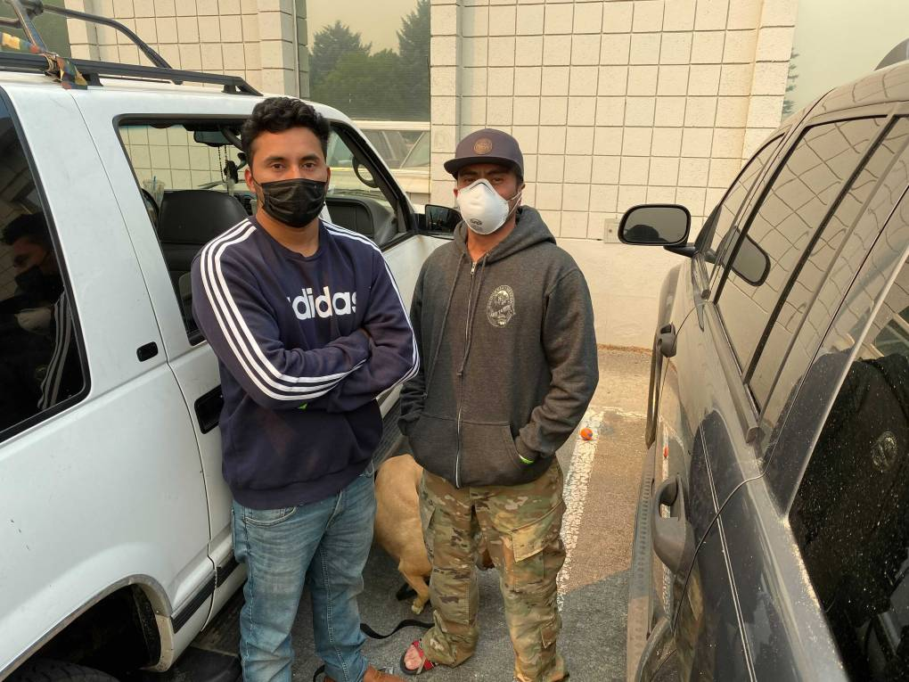 Two men wearing masks and sweatshirts pose between two parked vehicles.