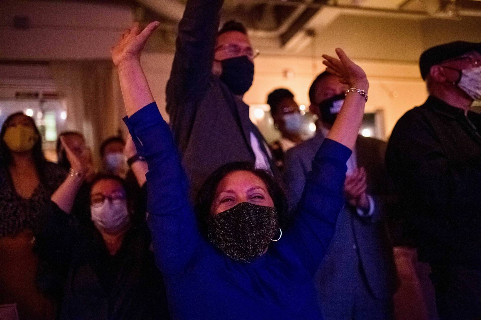 A group of masked Newsom supporters cheer and throw their hands in the air.