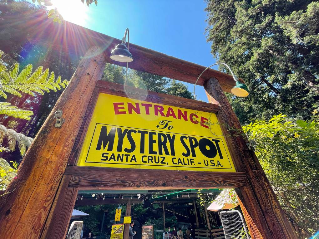 """A large yellow-and-black sign reads """"Welcome to Mystery Spot, Santa Cruz, California U.S.A."""""""