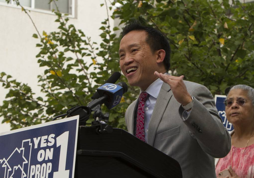 David Chiu, in a suit and tie, gestures as he speaks into a microphone at a podium.