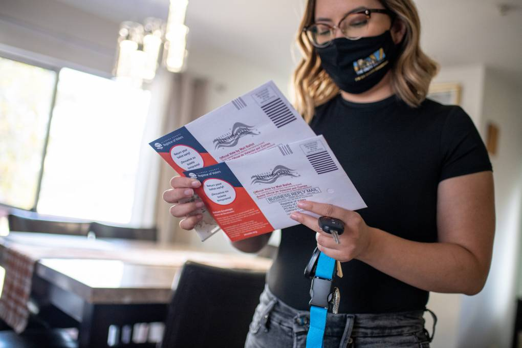 A woman wearing a mask and a T-shirt looks at her ballot.