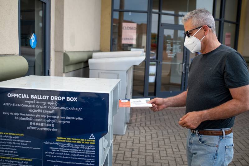 A man in a T-shirt and mask slides a ballot into a drop box.