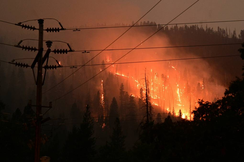 A silhouette of power lines in the foreground is backlit by a hillside on fire.