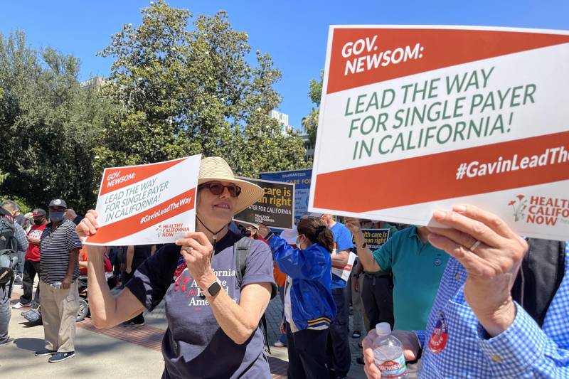 """Protesters hold up signs that read, """"Gov. Newsom: Lead the way for single payer in California!"""""""