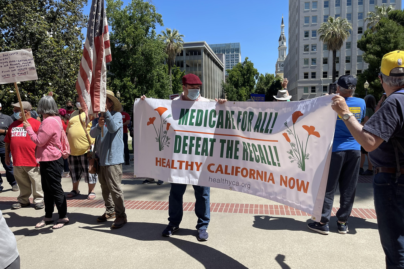 """Protesters hold up a sign that reads, """"Medicare for All! Defeat the Recall! Healthy California Now."""""""