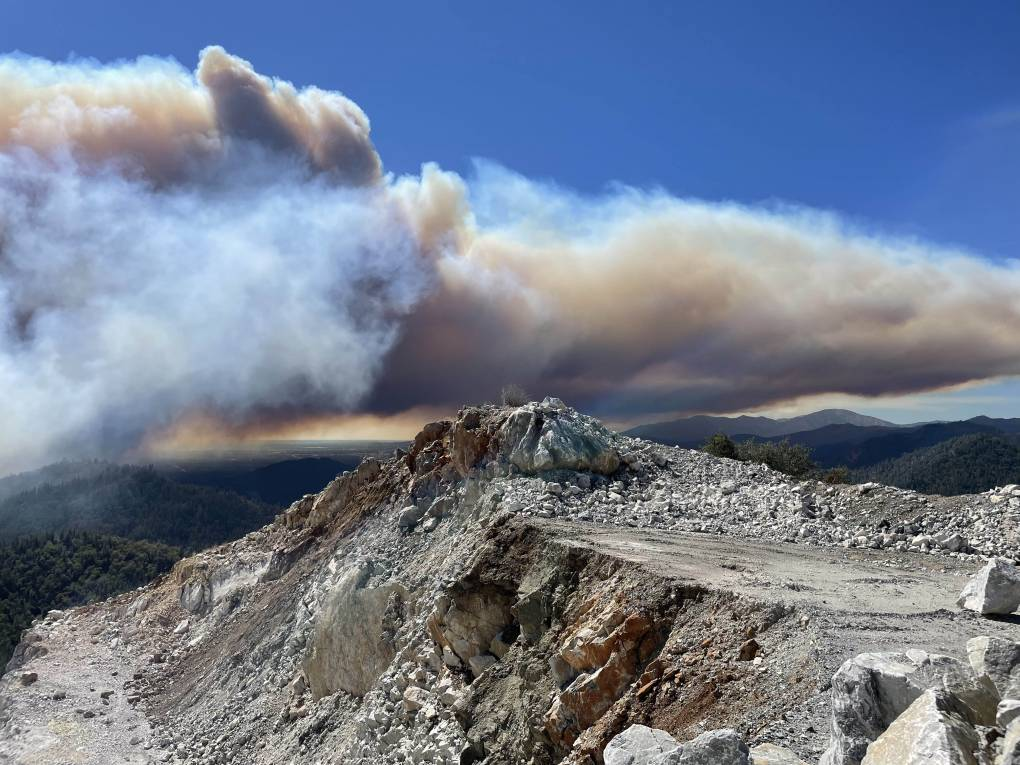 Gray smoke above granite ridges in a blue sky.