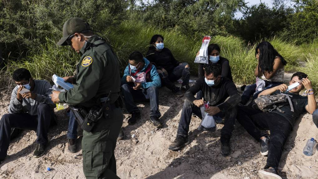 A U.S. border patrol agent in a green uniform stands over a group of migrants, who rest in the sand holding gallon jugs of water.