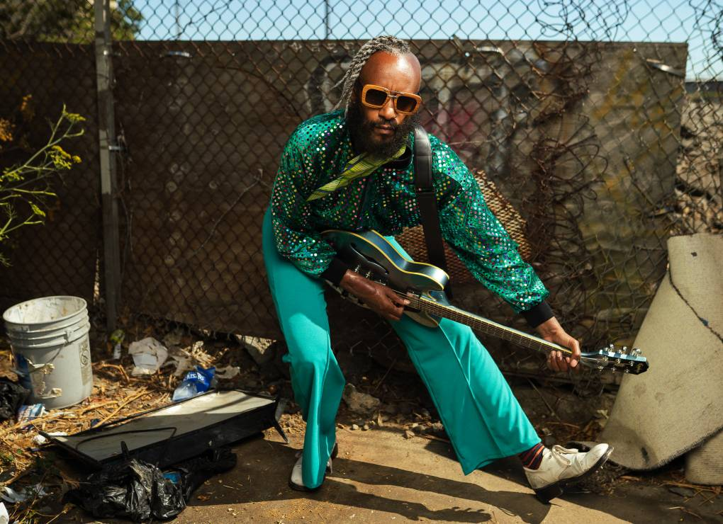 A man in a shiny, teal outfit and sunglasses crouches as he plays a green guitar.