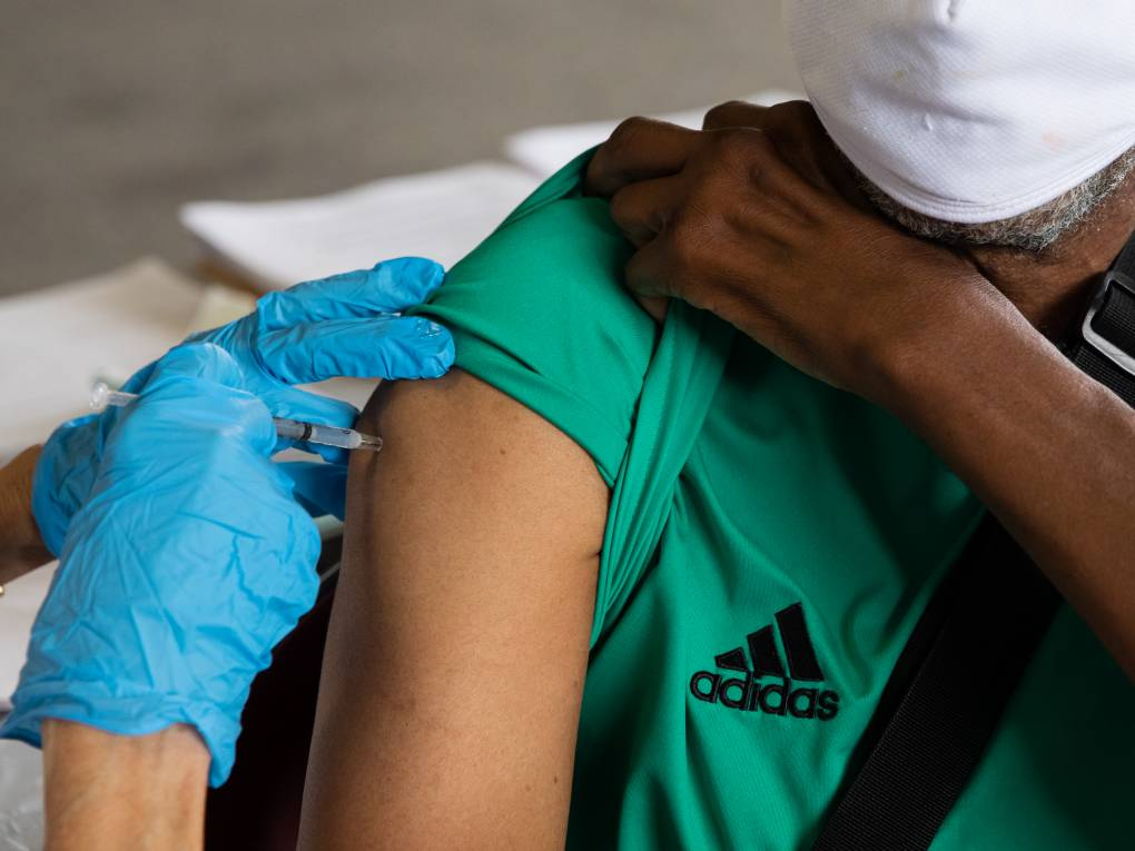 Blue-gloved hands administer a vaccine into a shoulder.