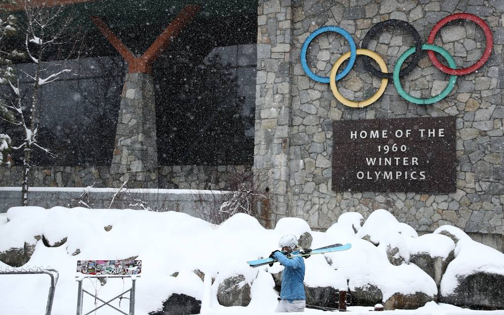 A skier in a bright blue ski outfit holding skis walks in the snow in front of a sign with the Olympic rings