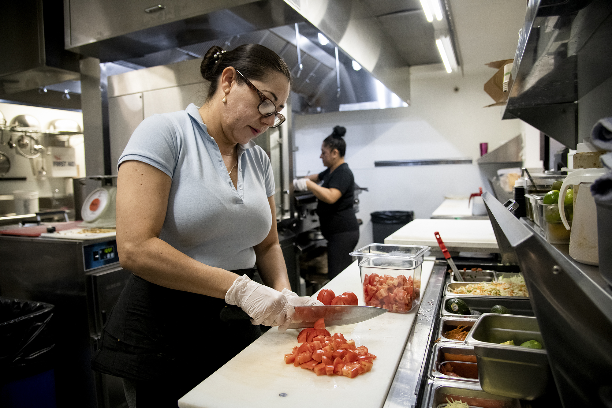 A woman with her hair back and wearing gloves chops tomatoes in a restaurant kitchen.