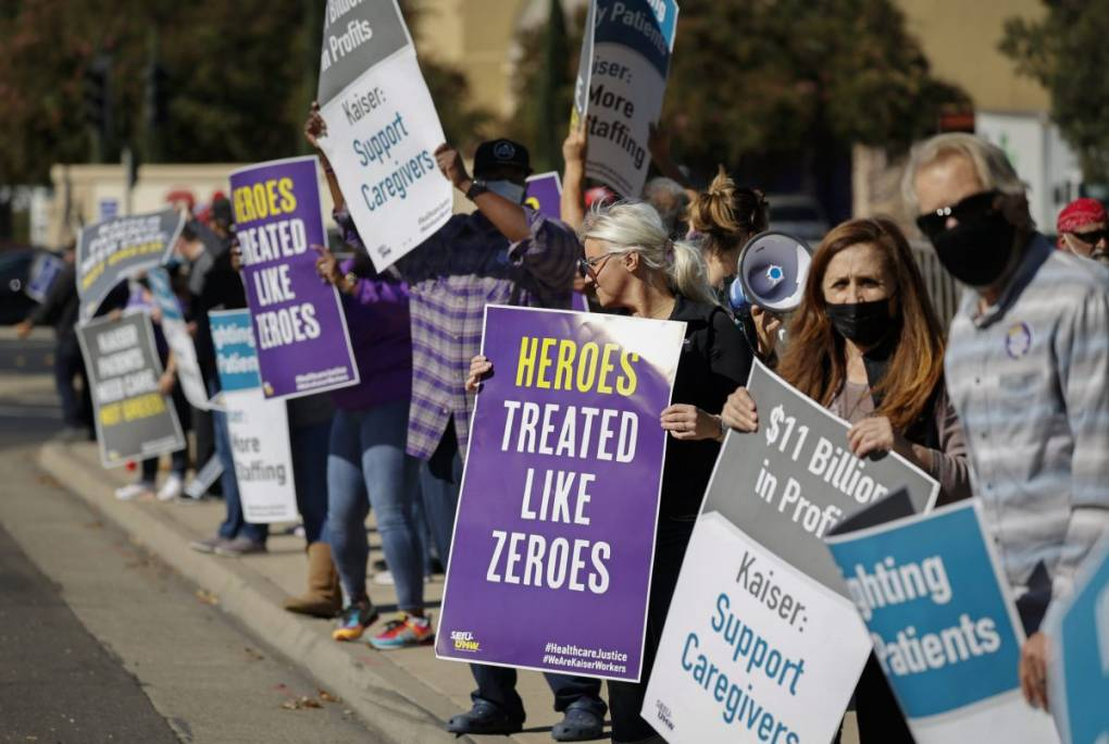 """Striking nurses holding signs read """"heroes treated like zeroes"""" and """"Kaiser: support caregivers."""""""