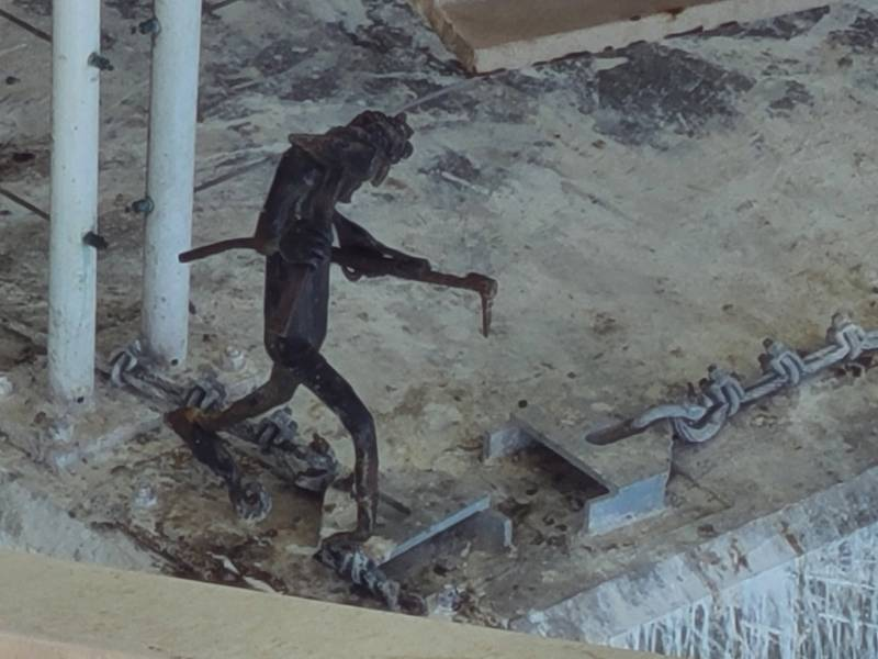 An angular dark metal figurine with legs and arms, holding tools, its feet affixed to the cement below it.