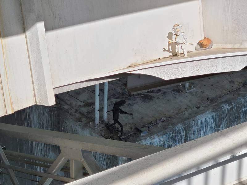 A view of painted white iron beams, with one metal figurine of a troll on a lower level in shadow, and a white-painted one in the light.