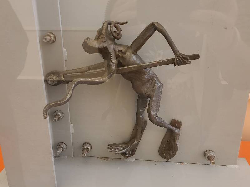A light-colored metal figurine with two arms and two legs, holding a very long wrench to turn a bolt.