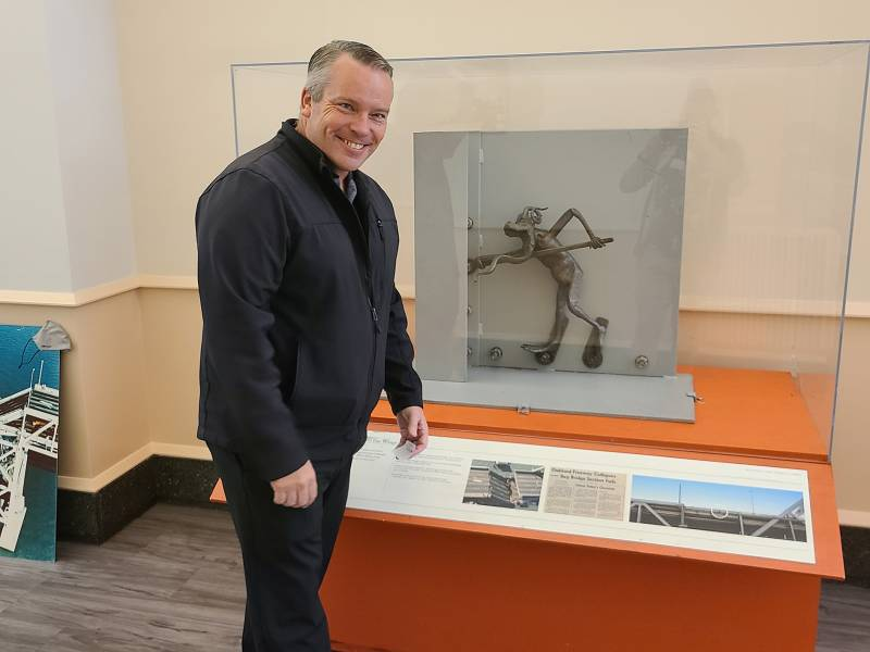 A smiling man in a black jacket and black pants poses in front of a glass case that hold a metal figurine of a fairly human-looking troll.