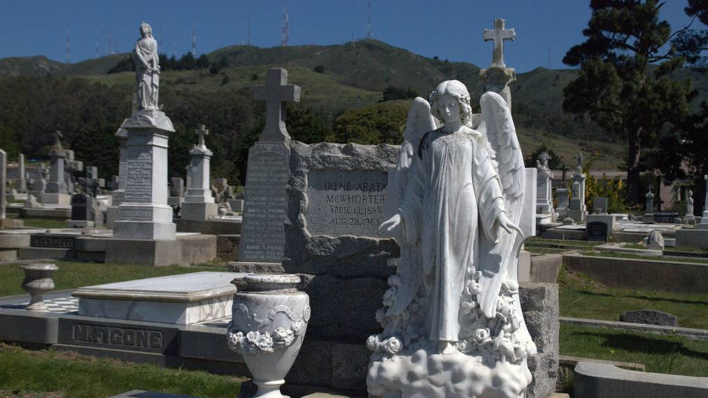 A stone statue of an angel in the foreground with many gravestones behind it.