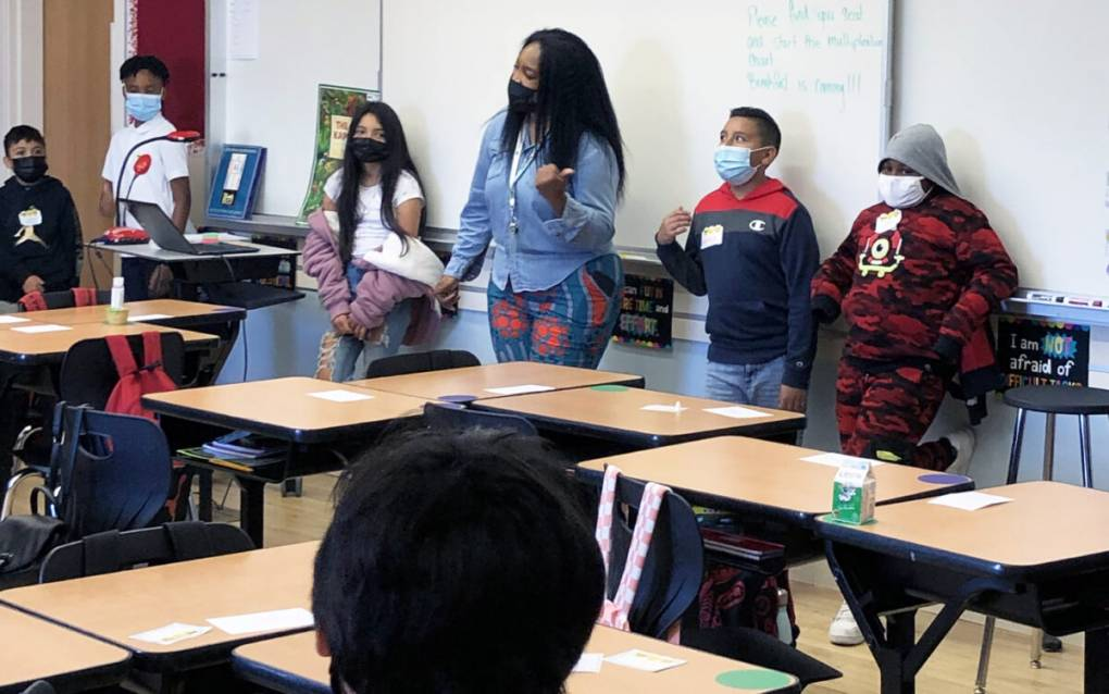 A woman flanked by kids in both directions stands at the front of a classroom against a whiteboard.