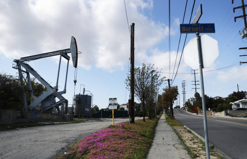 An oil drill stands still on the left; across the street to the right are homes.