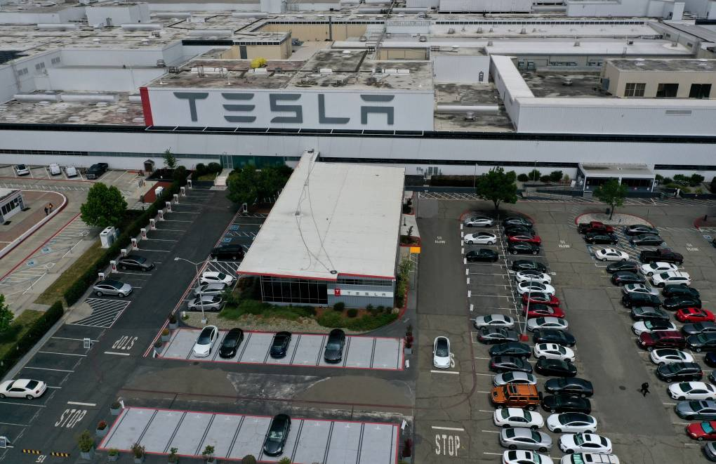 An aerial view of a long, flat building, a massive Tesla sign, and a massive parking lot.