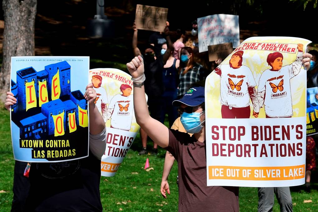 """Two protesters hold signs. One says, """"ICE Out: K-Town contra las redadas,"""" or K-Town against mass deportations; the other says """"Stop Biden's Deportations."""""""