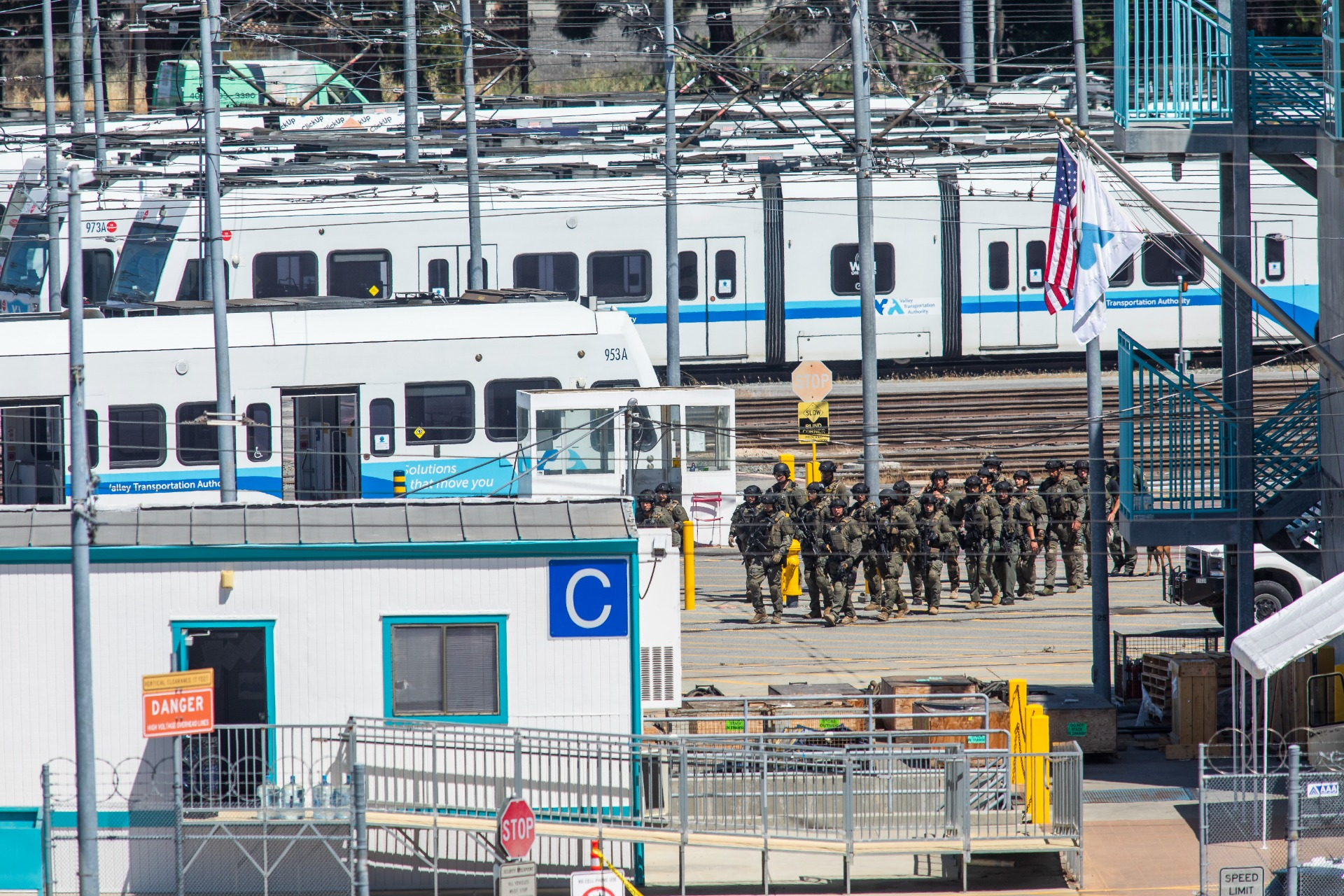 A faraway shot of a rail yard with a line of trains, as a small crowd of people in tactical gear walk toward the camera.