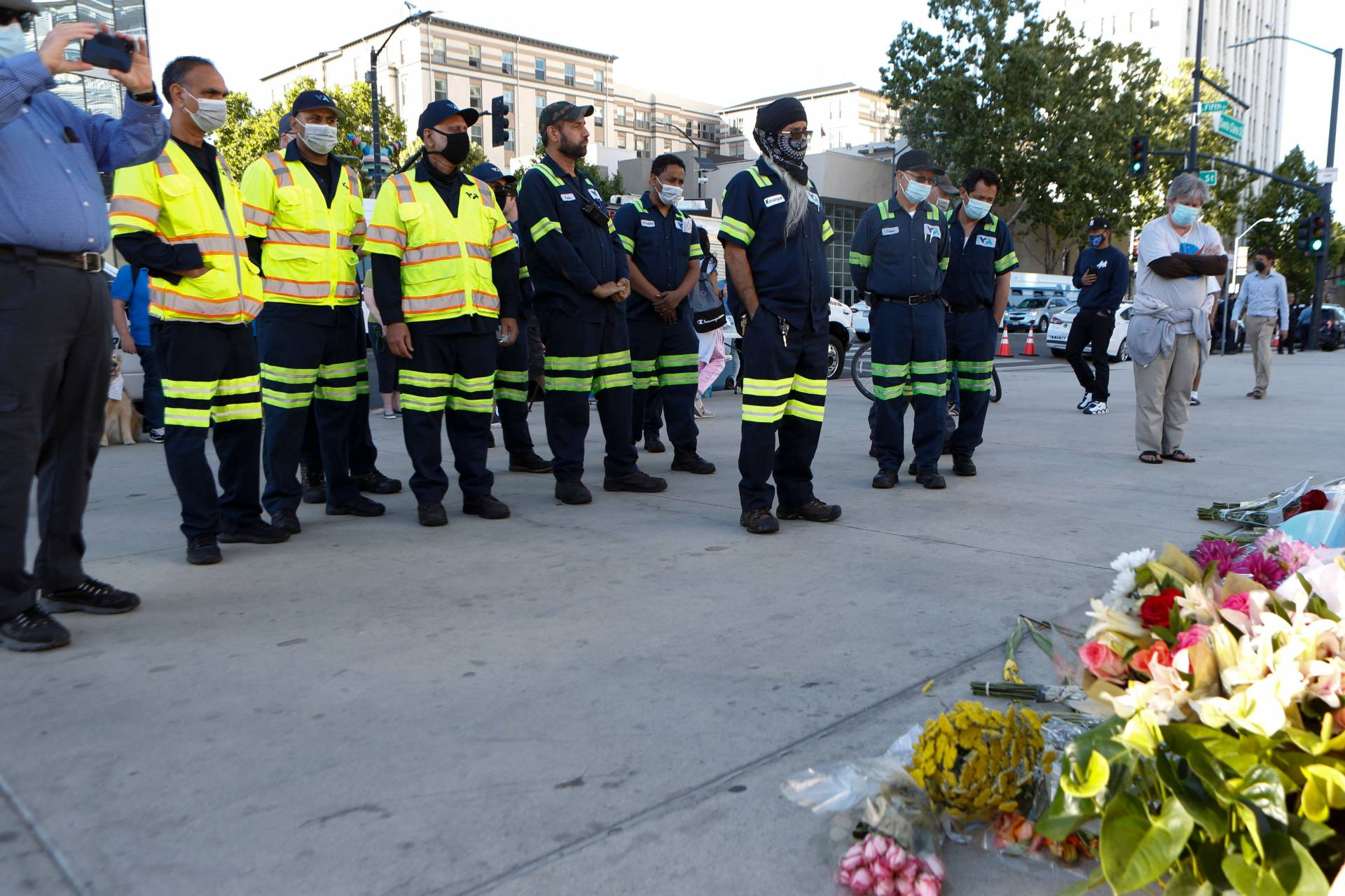 A line of people in uniform -- neon yellow jackets and dark blue pants with reflective stripes at the knees -- stand before a collection of flowers.